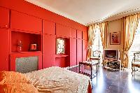 elegant bedroom with red walls and elegant gold accents with a queen-size bed, two armchairs, built-