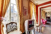 tastefully decorated 1-bedroom Paris luxury apartment in a traditional style, with gold, brown, and