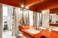 elegant bathroom with wooden sink counters, numerous mirrors, and pin lights, fully-equipped with a