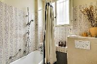 elegant bathroom with bathtub and detachable shower head in a 1-bedroom Paris luxury apartment