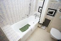 elegant bathroom with bathtub, toilet, and detachable shower head in a 1-bedroom Paris luxury apartm
