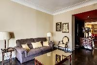 comfortable sofa bed, lamps, armchairs, and gold center table in a 1-bedroom Paris luxury apartment