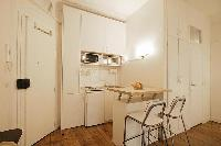 space efficient kitchen with breakfast bar and stools in a 1-bedroom Paris luxury apartment