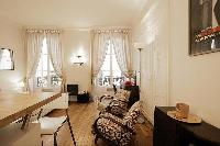 a space efficient studio Paris luxury apartment with immaculate white walls and golden oak floors