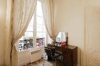 a dressing table with mirror and a chair tall windows, and drape curtains in a 1-bedroom Paris luxur