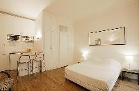 sleeping area with two bedside tables, two lamps, and a double bed in a 1-bedroom Paris luxury apart
