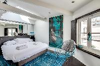first bedroom in aqua, white and gray hues, furnished with a king-size bed with built-in shelves, an