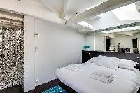 first bedroom with a king-size bed and en suite bathroom in Paris luxury apartment