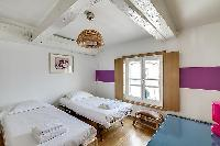 second bedroom in purple and fuschia hues furnished with two single beds, a few chairs, a desk, and