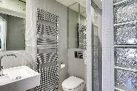 second bathroom fully-furnished with a toilet, a sink, and a shower area in Paris luxury apartment