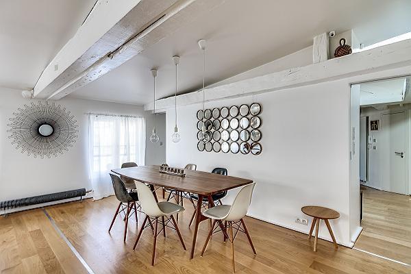 dining area with a long wooden table and six modern chairs in Paris luxury apartment