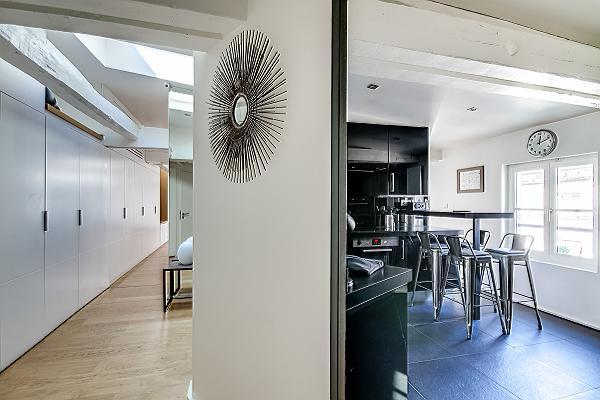 hallway filled with closets and spacious and monochromatic kitchen in Paris luxury apartment