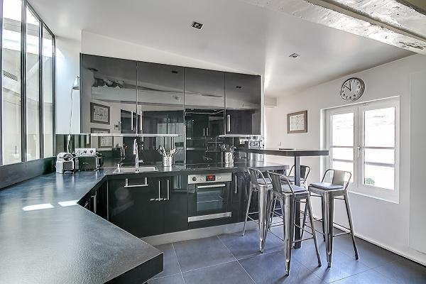 spacious kitchen with a small kitchen counter with four seats in Paris luxury apartment