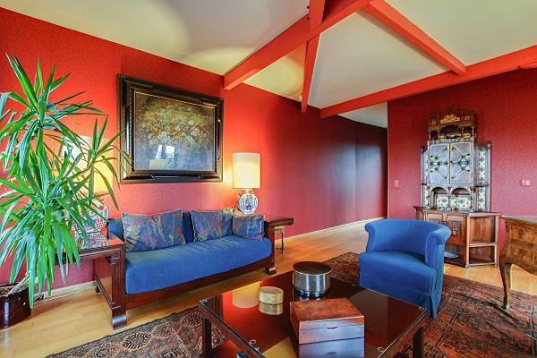 elegant living area with rich red walls, a blue sofa, a matching armchairs, and a few desks in a 3-b