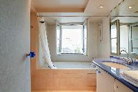 an en-suite bathroom with a toilet, a sink, a built-in cabinet, a mirror, and a bathtub in a 3-bedro