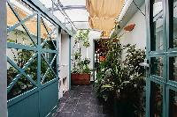 lovely patio with numerous plants illuminated by the skylight in a 3-bedroom Paris luxury apartment