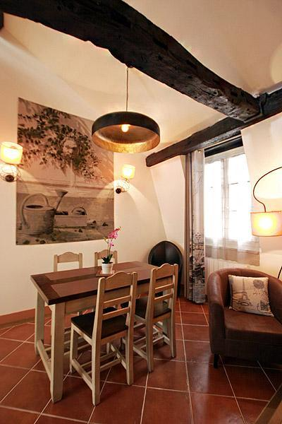 lovely dining area with wooden table and chairs for 4, exposed beams, and paintings in a 2-bedroom P