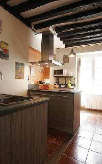 modern well-equipped kitchen with breakfast bar and stools in a 2-bedroom Paris luxury apartment