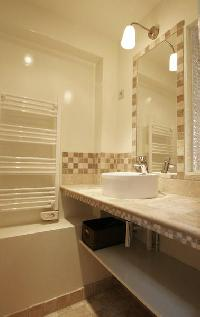 first bathroom with tiled floor, shower, sink, hairdryer, and separate toilet in a 2-bedroom Paris l