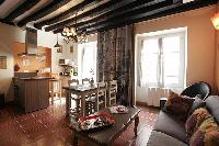 cozy living area, dining area and kitchen with exposed beams in a 2-bedroom Paris luxury apartment
