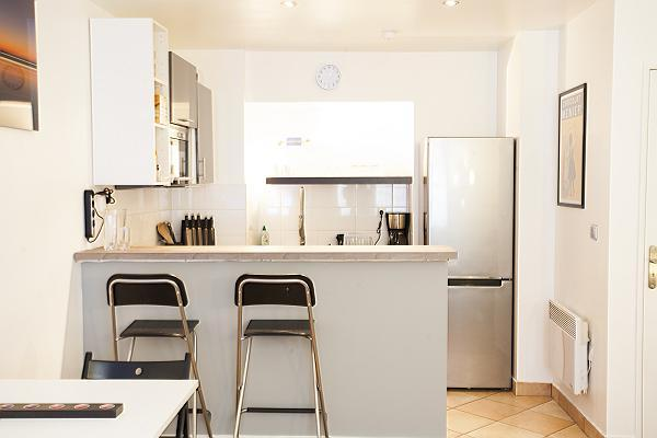 monochromatic and space-efficient kitchen with breakfast bar and stools in a 1-bedroom Paris luxury