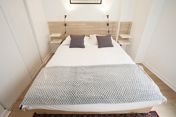 modern bedroom with bedside tables, lamps, and a queen-size bed in a 1-bedroom Paris luxury apartmen