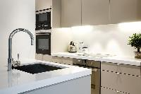 modern yet classy kitchen with breakfast bar and stools in Paris luxury apartment