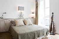 elegant bedroom with built-in cabinets, lamps and queen-size bed in a 2-bedroom Paris luxury apartme