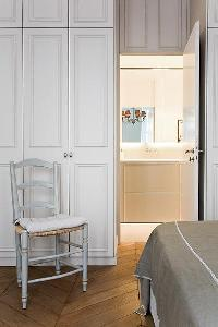 elegant bedroom with built-in cabinets, chair, queen-size bed an e suite bathroom in a 2-bedroom Par
