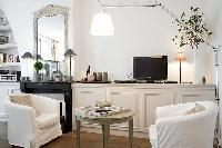 classy living area with two armchairs, a table, a television, and a fireplace in Paris luxury apartm