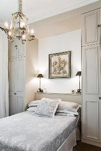 classy bedroom with built-in closets, lamps, and queen-size bed  in Paris luxury apartment