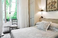 classy bedroom with built-in closets, lamps, chair, and queen-size bed  in Paris luxury apartment