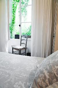classy bedroom with  a chair, French window with potted plants and queen-size bed in Paris luxury ap