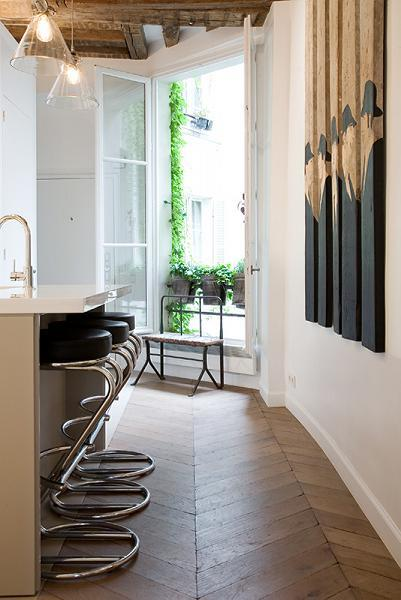 French window with potted plants, breakfast bar and stools in Paris luxury apartment