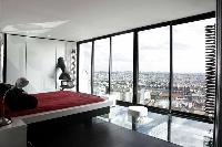 minimalist bedroom with queen-size bed and skyline view of Paris