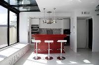 modern kitchen counter with three stools in a 3-bedroom Paris luxury apartment