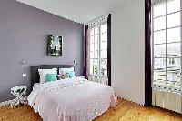 spacious first bedroom with a queen-size bed in a 3-bedroom Paris luxury apartment