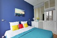 cozy bedroom with a double bed in blue and white hues in a Paris luxury apartment