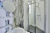 stylish bathroom with a toilet, sink, shower, and a bathtub in a 3-bedroom Paris luxury apartment