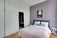 spacious bedroom with a queen-size bed in a 3-bedroom Paris luxury apartment