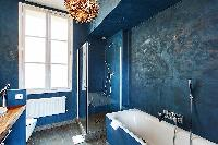 stylish bathroom in blue hue with a toilet, sink, shower, and a bathtub in a 3-bedroom Paris luxury