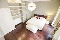 spacious master's bedroom with shelves and a queen-size bed  in a 2-bedroom Paris luxury apartment