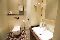 water closet with a toilet and a sink in a 2-bedroom Paris luxury apartment