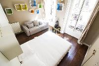 bedroom with built-in closets, a sofa, and a double bed  in a 2-bedroom Paris luxury apartment