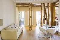 modern living room  and dining area with exposed beams in a 2-bedroom Paris luxury apartment