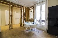 dining area with a glass table and four chairs in a 2-bedroom Paris luxury apartment