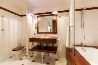 second bathroom with white tiles and wood paneling equipped with a toilet, a sink, and a bathtub in