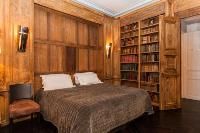master bedroom with wood paneling and bookshelves with leather-bound books, fireplace, and a desk wi