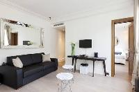 cozy living area with a large black sofa and a chair in a  studio Paris luxury apartment