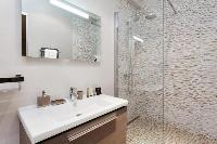 an en-suite bathroom with a sink, toilet, and shower area in a 4-bedroom Paris luxury apartment